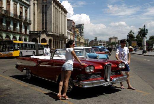 Turistas posando en un carro clásico americano en La Habana, Cuba. Desde el deshielo con Estados Unidos aumentó cerca de 20% la cantidad de turistas en la isla y también las recaladas de los cruceros