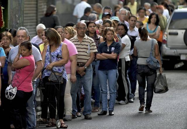 Un grupo de personas hace fila para comprar en una tienda de Caracas.
