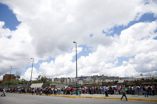 People wait in a line to buy staple goods outside a state-run Bicentenario supermarket in Caracas