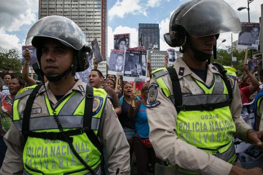 VEN42 - CARACAS (VENEZUELA), 10/9/2015.- Un cordón policial separa al grupo de seguidores del opositor venezolano Leopoldo López, y otro grupo oficialista hoy, jueves 10 de septiembre de 2015, frente al palacio de Justicia donde se espera que se dicte sentencia en el caso que se sigue contra López por hechos relacionados con las protestas antigubernamentales de 2014 en Caracas (Venezuela). Seguidores oficialistas, alrededor de 300, se encontraban separados por un cordón policial, de otros tantos simpatizantes opositores y ambos comenzaron en un momento a enfrentarse a gritos y lanzarse objetos, aunque la situación se calmó a los pocos minutos, una vez que los familiares del opositor accedieron al Palacio de Justicia. EFE/ FABIOLA FERRERO