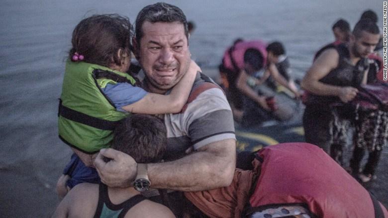 Un refugiado sirio carga a su hija mientras llora de alegría cuando su embarcación finalmente llegó a la isla griega de Kok el 15 de agosto.