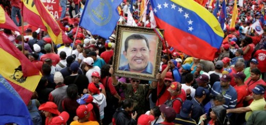 A supporter of Venezuela's President Nicolas Maduro holds a portrait of Venezuela's late President Hugo Chavez, during a rally to commemorate May Day, in Caracas, Venezuela, May 1, 2016. REUTERS/Marco Bello
