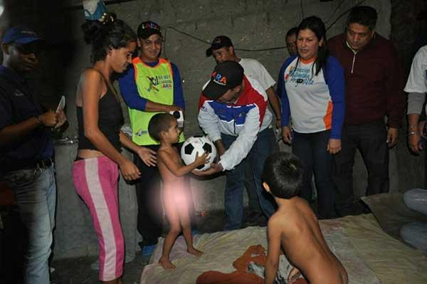 Momento en que el Gobernador Henri Falcón hace entrega de un balón de fútbol a uno de los niños de una familia en extrema pobreza en Lara | Foto: Henri Falcón