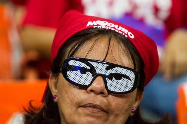 Una mujer porta unos lentes con una imagen de los ojos del fallecido presidente venezolano Hugo Chavez | EFE