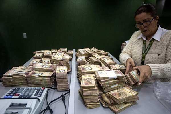 Empleados bancarios cuentan los fajos de billetes de 100 bolívares que las personas quieren cambiar porque un decreto presidencial decidió que salieran de circulación. | Foto: Miguel Gutierrez / European Pressphoto Agency