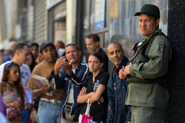 Un soldado venezolano resguarda la sede de un banco en Caracas mientras la gente hace largas filas para cambiar sus billetes, el 15 de diciembre. Foto: Federico Parra / AFP