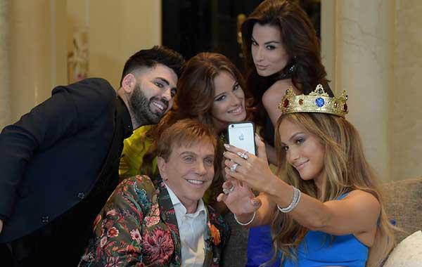 Jennifer López se hace un selfie con Osmel Sousa (chaqueta estampada) y otros en la mansión de Univision donde se graba el reality de misses 'Nuestra Belleza Latina' en Miami, en 2013 | Foto: Getty Images