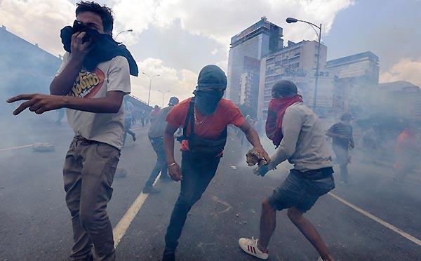 Manifestantes con capucha en la protesta del 6 de abril | Foto: EPA