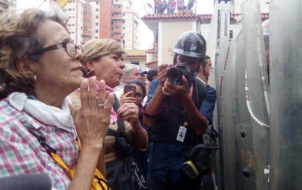 Mujeres colocan rosarios en escudos de la GNB que impiden el paso en El Paraíso | Foto: @unidadvenezuela