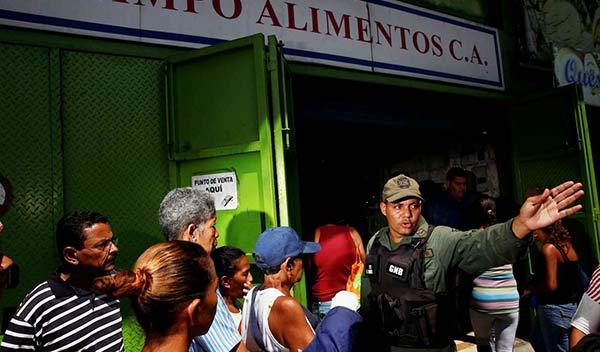 Soldado trata de poner orden en una cola para comprar comida (07/19/2016)   REUTERS/Carlos Garcia Rawlins