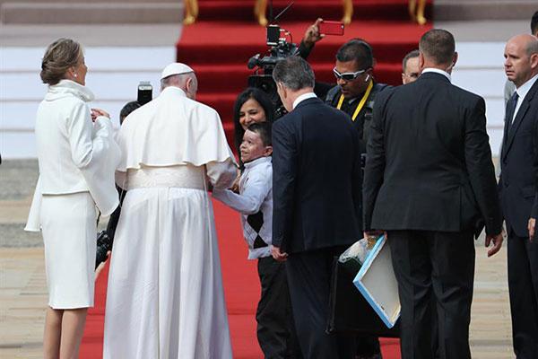 Niño se salta el protocolo para entregarle una bandera de Venezuela al Papa | Foto: EFE