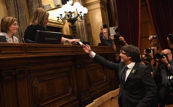 El presidente de la Generalitat, Carles Puigdemont, entrega su voto en el Parlament | AFP