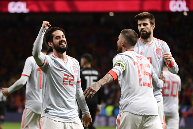 Spain's midfielder Isco (L) celebrates with Spain's defender Gerard Pique (R) and Spain's defender Sergio Ramos after scoring a goal during a friendly football match between Spain and Argentina at the Wanda Metropolitano Stadium in Madrid on March 27, 2018. / AFP PHOTO / PIERRE-PHILIPPE MARCOU