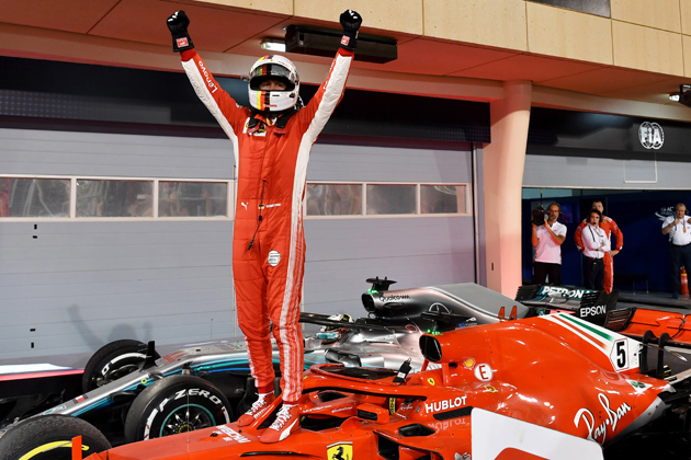Ferrari's German driver Sebastian Vettel celebrates on his car after winning the Bahrain Formula One Grand Prix at the Sakhir circuit in Manama on April 8, 2018.  / AFP PHOTO / Andrej ISAKOVIC